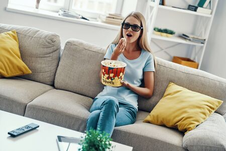Beautiful young woman watching TV in 3-D glasses and eating popcorn while relaxing on the sofa at home