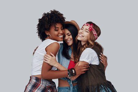 Drei attraktive, stilvolle junge Frauen, die sich umarmen und lachen, während sie vor grauem Hintergrund stehen Standard-Bild
