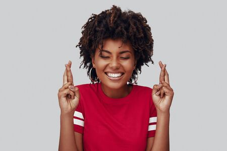 Attractive young African woman keeping fingers crossed and smiling while standing against grey background Banque d'images - 128612060