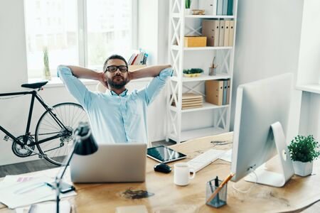 Relaxed middle age man in smart casual wear keeping hands behind head while sitting in the office Stock Photo