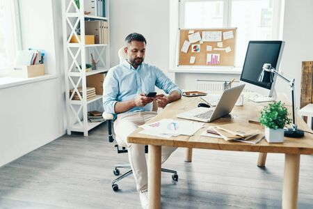 Thoughtful middle age man in smart casual wear using mobile phone while sitting in the office