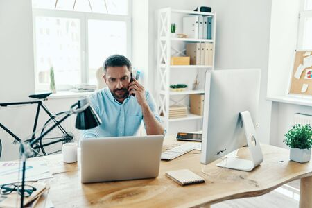 Handsome middle age man in smart casual wear using laptop and talking on the phone while sitting in the office Stock Photo