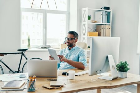 Handsome middle age man in smart casual wear using digital tablet and smiling while sitting in the office Stock Photo