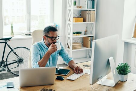 Handsome middle age man in smart casual wear using computer and drinking coffee while sitting in the office Stock Photo
