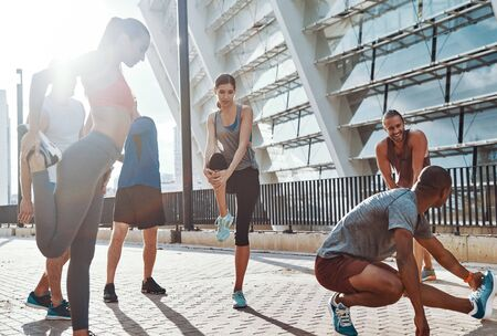 Full length of people in sports clothing warming up and stretching while exercising on the sidewalk outdoors 写真素材