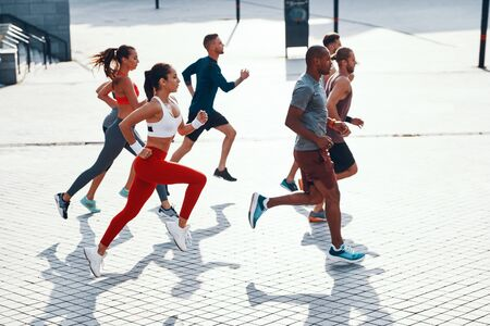 Full length top view of people in sports clothing jogging while exercising on the sidewalk outdoors