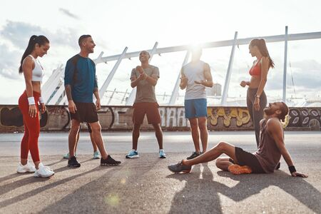Full length of young people in sports clothing relaxing while exercising outdoors
