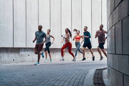 Full length of people in sports clothing jogging while exercising outdoors