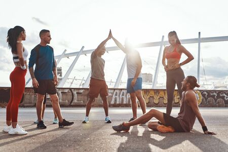 Full length of people in sports clothing encouraging each other while exercising outdoors 写真素材