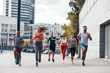 Full length of people in sports clothing jogging while exercising on the sidewalk outdoors
