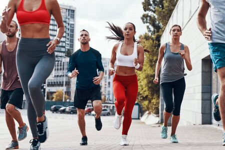 Group of young people in sports clothing jogging while exercising on the sidewalk outdoors