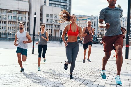 Group of people in sports clothing jogging while exercising on the sidewalk outdoors