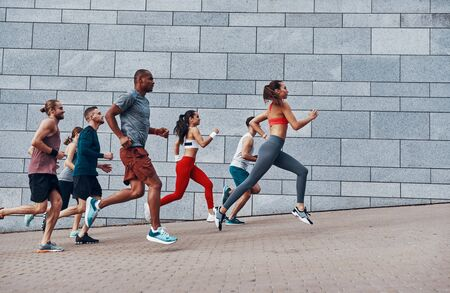 Full length of people in sports clothing jogging while exercising on the sidewalk outdoors Stock Photo