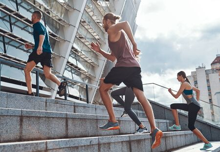 Full length of young people in sports clothing jogging while exercising on the stairs outdoors