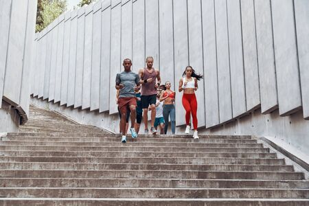 Full length of people in sports clothing jogging while exercising on the steps outdoors