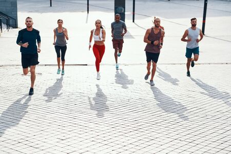 Full length top view of people in sports clothing jogging while exercising on the sidewalk outdoors 写真素材