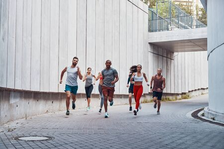 Full length of young people in sports clothing jogging while exercising outdoors
