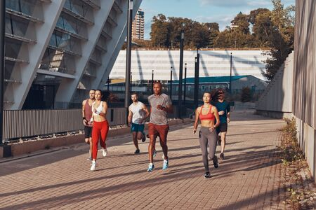 Full length of young people in sports clothing jogging together outdoors