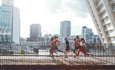 Full length of young people in sports clothing jogging while exercising on the bridge outdoors