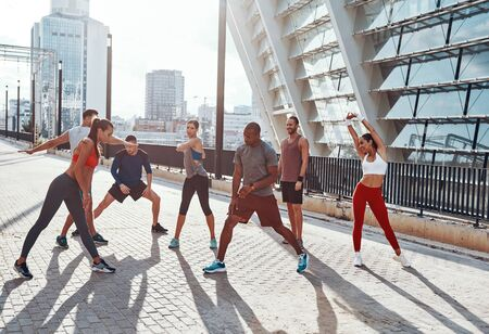 Full length of people in sports clothing warming up and stretching while exercising outdoors
