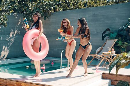 Full length of attractive young women in swimwear having fun with squirt guns while standing on the poolside outdoors