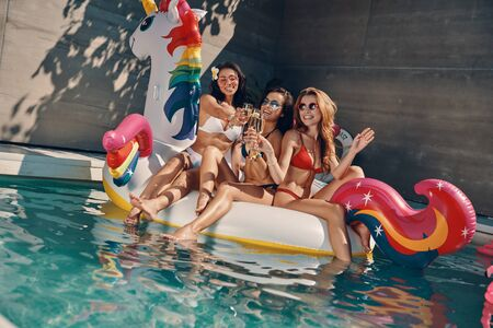 Attractive young women in swimwear smiling and drinking champagne while floating on inflatable unicorn in swimming pool outdoors Stock Photo