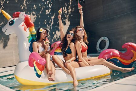 Attractive young women in swimwear smiling and eating watermelon while floating on inflatable unicorn in swimming pool outdoors