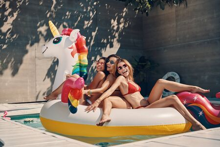 Attractive young women in swimwear smiling while floating on inflatable unicorn in swimming pool outdoors Stock fotó