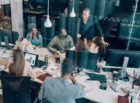 Top view of young modern people in smart casual wear communicating and using modern technologies while working in the office