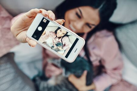 Top view of beautiful young woman in pajamas embracing domestic cat and taking selfie while resting in bed at home    Reklamní fotografie