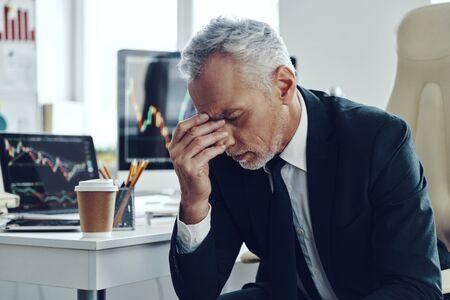 Homme senior frustré dans une entreprise élégante souffrant de maux de tête en travaillant au bureau