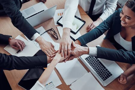 Top view of cheerful business team keeping hands together as a symbol of unity while working together in the modern office