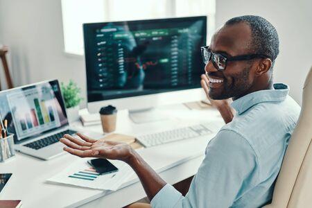 Beau jeune homme africain en chemise à l'aide d'un ordinateur et souriant tout en travaillant au bureau