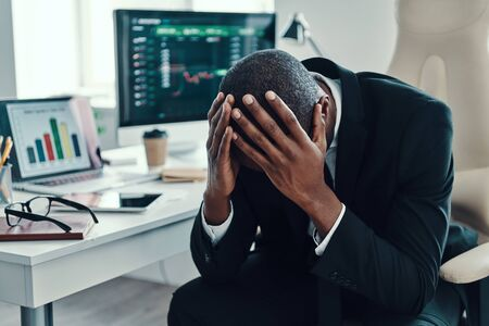 Tired young African man in formalwear keeping head in hands while working in the office                  Standard-Bild