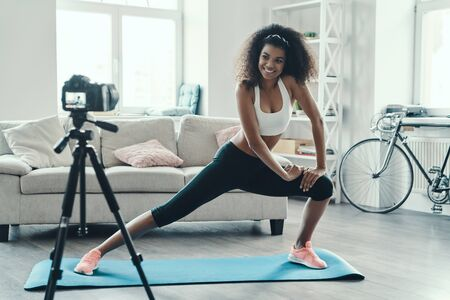 Beautiful young African woman working out and smiling while making social media video