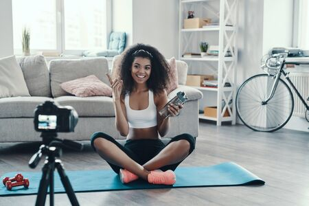 Fit young African woman working out and smiling while making social media video