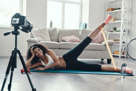 Happy young African woman exercising using strap and smiling while making social media video