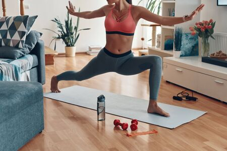Close up of slim young woman in sports clothing working out while spending time at home