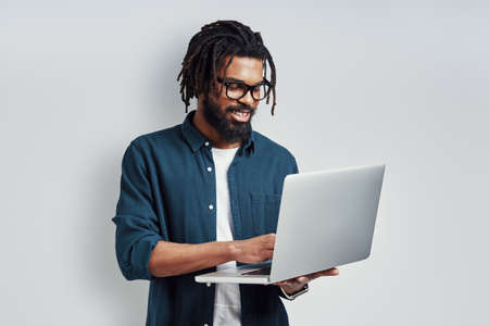 Happy young African man in eyewear using laptop while standing against grey background