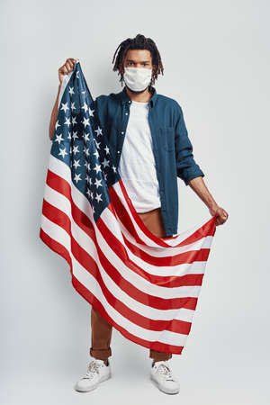 Handsome young African man carrying American Flag wearing medical face mask and looking at camera while standing against grey background