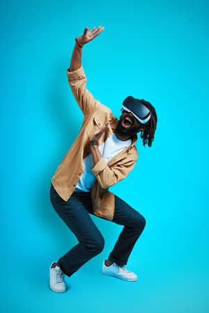 Full length of playful young African man wearing virtual reality glasses while standing against blue background 免版税图像
