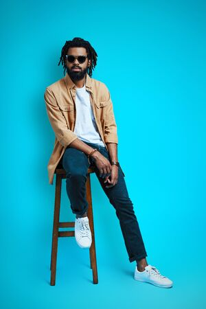 Full length of charming young African man in casual wear looking at camera while sitting on stool against blue background 免版税图像