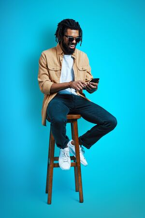 Full length of charming young African man in casual wear using smart phone while sitting against blue background