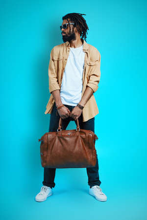 Full length of young African man in casual wear carrying leather bag and looking away while standing against blue background