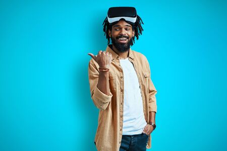 Happy young African man in virtual reality glasses pointing copy space and smiling while standing against blue background