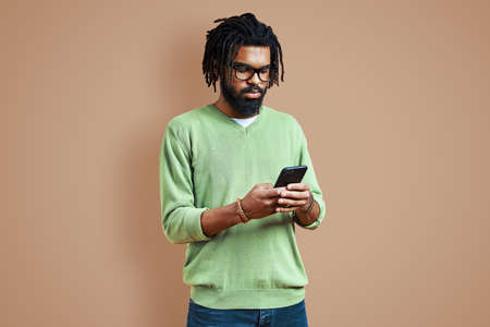 Thoughtful young African man in smart casual clothing using smart phone while standing against brown background