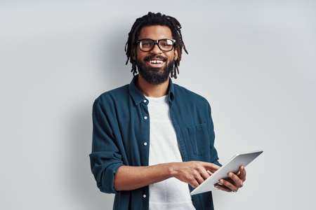 Charming young African man in eyewear using digital tablet and smiling while standing against grey background