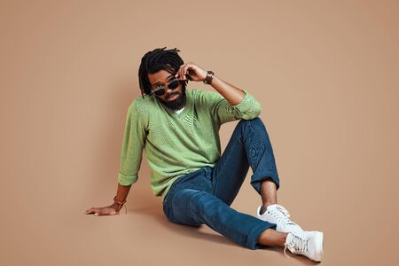 Trendy young African man in casual clothing looking at camera and adjusting eyewear while sitting against brown background