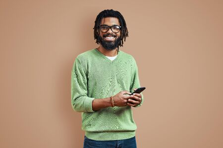 Happy young African man in smart casual clothing using smart phone while standing against brown background