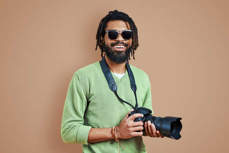 Young African photographer in casual clothing looking at camera and smiling while standing against brown background 免版税图像